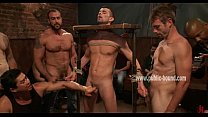 Man is bound in a medieval device, tied up and jerked off by dominati