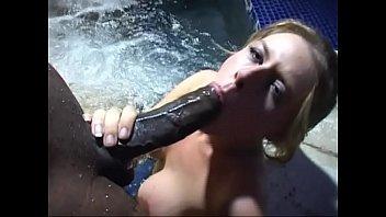 Slutty blonde sucks a huge black cock in a pool