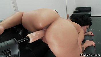 Brunette fucks machine on the sofa