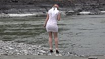 Juicy ass and slender legs under a short narrow dress outdoors in a public place. Russian beauty exposes her intimate places while walking along the riverbank.