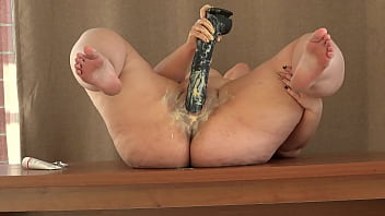 Mature BBW smears cream on her plump figure and masturbates with a huge black rubber dick on the table Homemade fetish and big shaved pussy